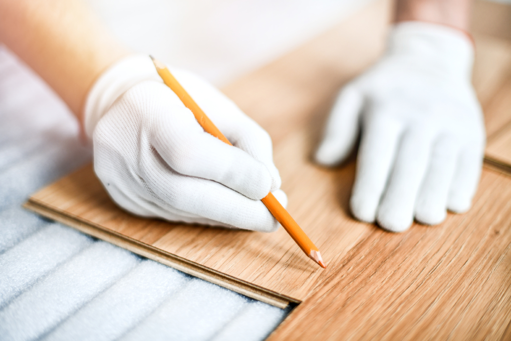 Close up of wood worker with in white gloves measuring tape and new laminated wooden floor board.